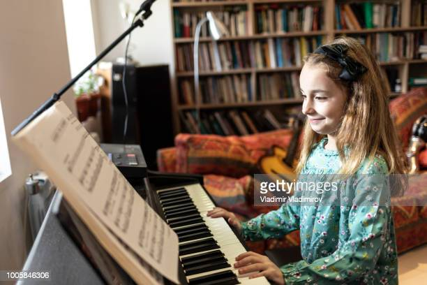 cute little girl playing the piano - electric piano stock photos and pictures