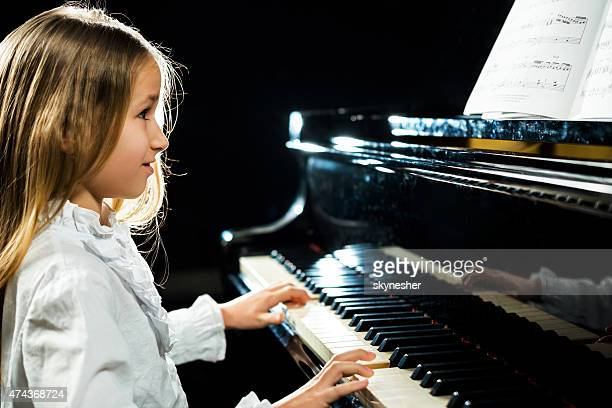 Cute little girl playing the piano.