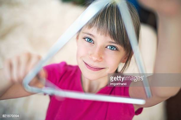 cute little girl playing triangle - triangle percussion instrument stock photos and pictures