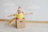 Cute little girl playing with cardboard airplane in living room