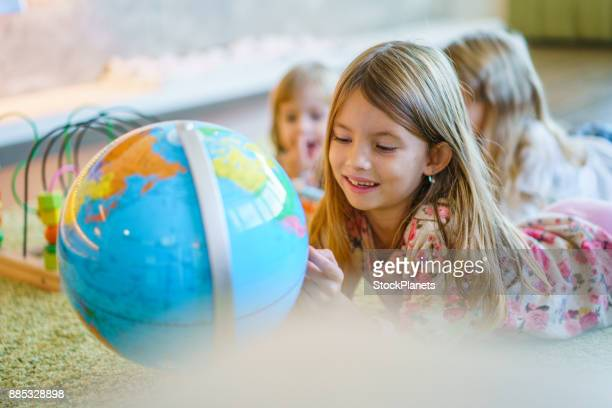 Cute little girl playing with globe