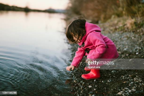 Cute Little Girl Plays At River Shoreline