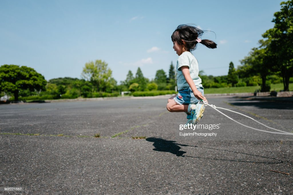Cute little girl practicing jump rope at the park : Stock Photo