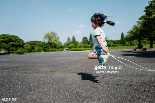 cute little girl practicing jump rope at the park - drive sportbegriff stock-fotos und bilder