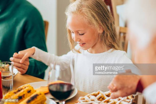cute little girl prays before a holiday dinner. - religious blessing stock pictures, royalty-free photos & images