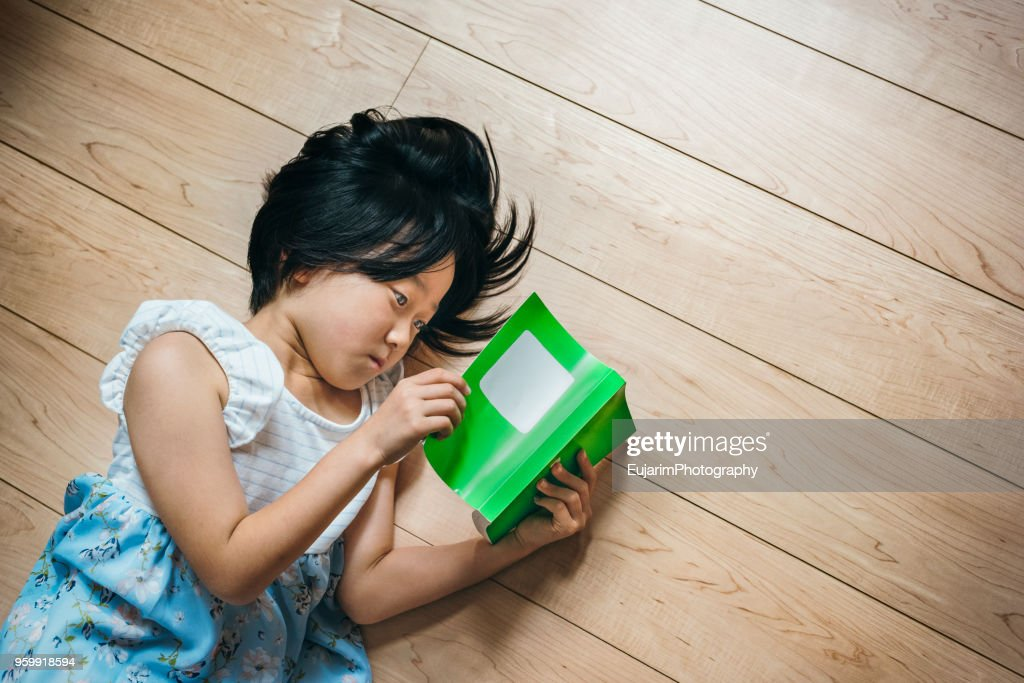 Cute little girl reading book on the floor : Stock Photo