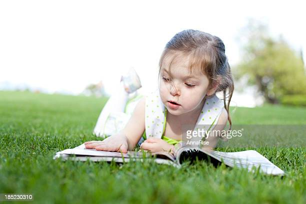 cute little girl reading magazine - nature magazine stock pictures, royalty-free photos & images