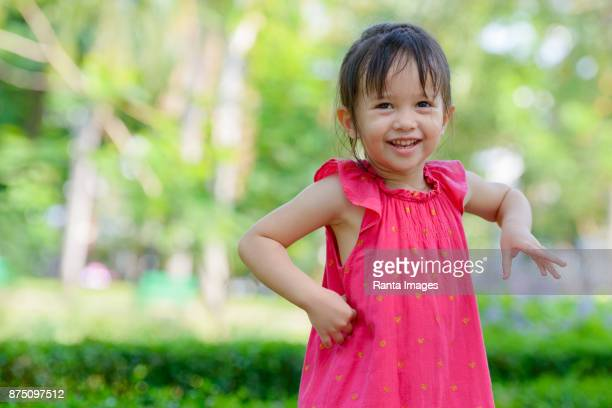cute little girl relaxing at lumpini park in the city of bangkok thailand - pink dress stock pictures, royalty-free photos & images