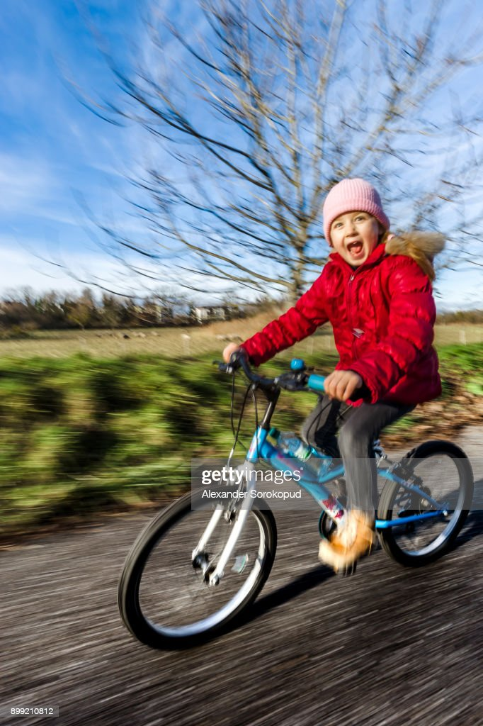 Cute little girl riding by bike sunny day in countryside, speed and motion