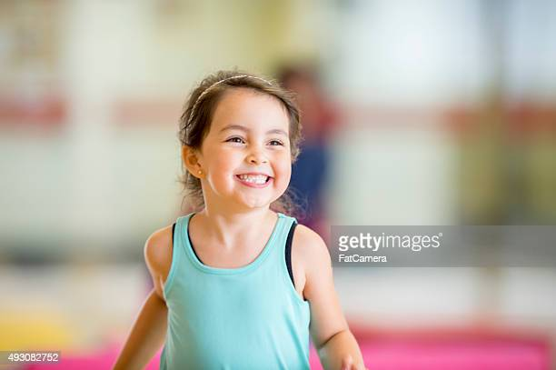 cute little girl running in the gym - gymnastiek stockfoto's en -beelden