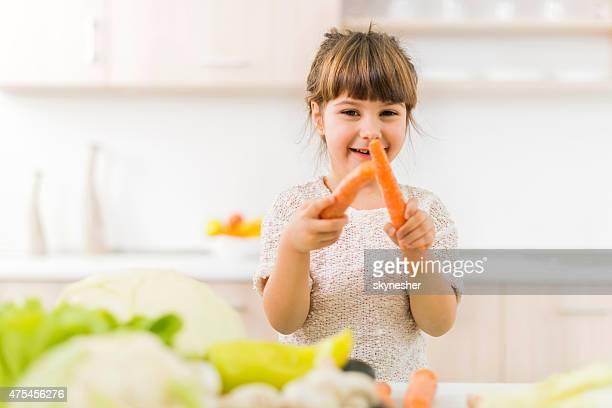 Niedliche kleine Mädchen sitzt in der Küche und holding Peitsche.