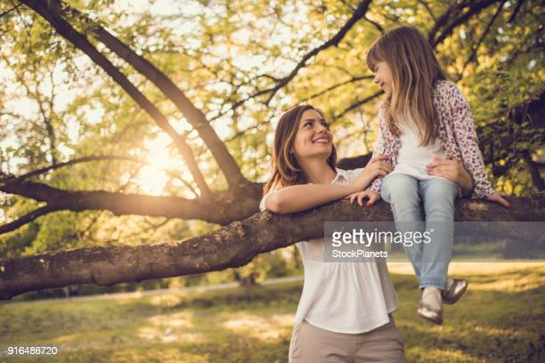 Cute little girl sitting on tree branch and looking at mother