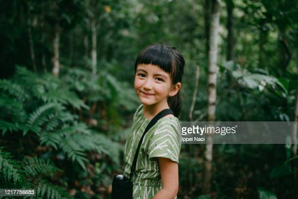 cute little girl smiling at camera in rainforest, iriomote, okinawa, japan - brown eyes stock pictures, royalty-free photos & images