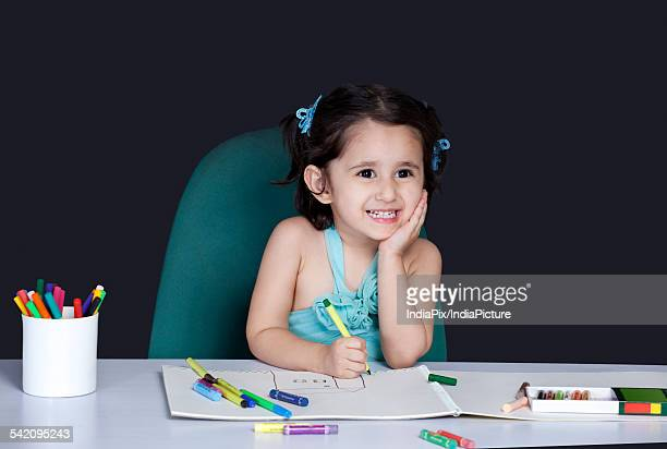 Cute little girl smiling while drawing