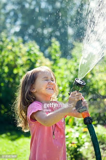Niedlich kleines Mädchen sprühen Wasser über sich selbst im Garten