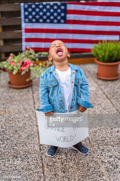 cute little girl standing in the rain and holding a poster with a message: i am gonna change the world! - racism stock pictures, royalty-free photos & images