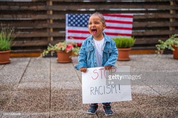 cute little girl standing in the rain and holding a poster with a message: stop racism! - social justice concept stock pictures, royalty-free photos & images