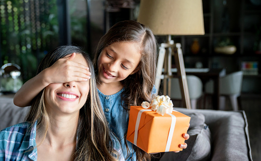 Cute little girl surprising her mom with a gift box for mother's day while covering her eyes 1023053364
