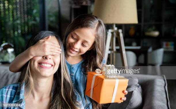 cute little girl surprising her mom with a gift box for mother's day while covering her eyes - festa della mamma foto e immagini stock
