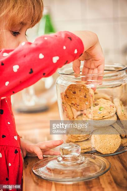 Cute Little Girl Taking Chocolate Chip Cookie From Jar