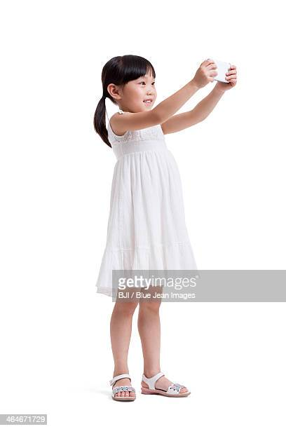 Cute little girl taking pictures with smart phone