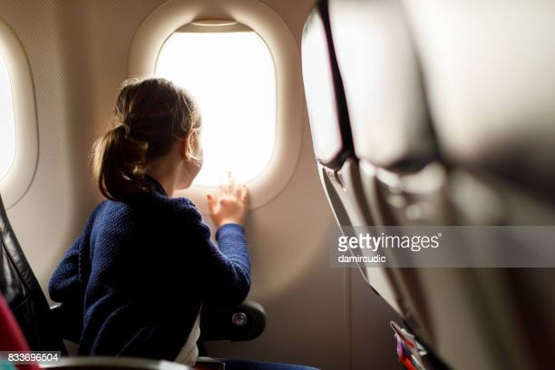 cute little girl traveling by an airplane - aeroplane stock pictures, royalty-free photos & images