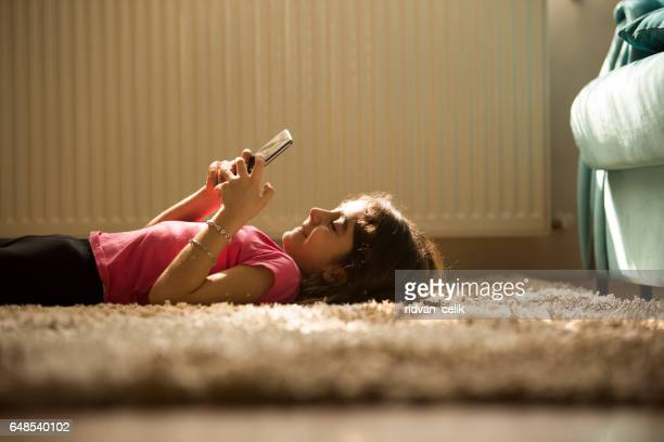 cute little girl using mobile phone at home - petite teen girl stock photos and pictures