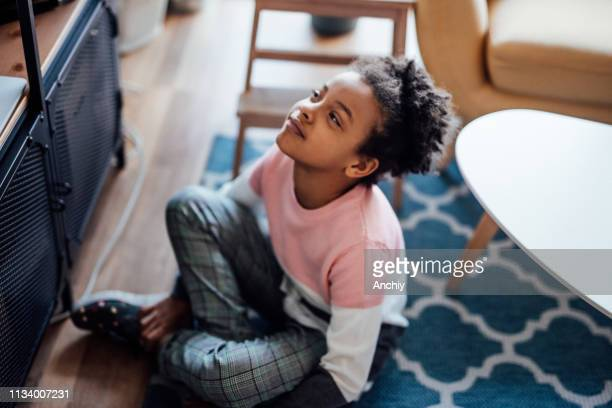 Cute little girl watching TV at home