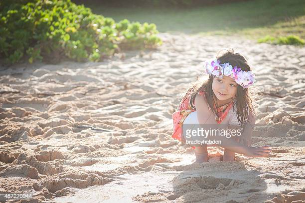 cute little girl wearing a lei plays on hawaiian beach - lei day hawaii stock pictures, royalty-free photos & images