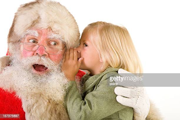 cute little girl whispers in surprised santa's ear - santa face stock pictures, royalty-free photos & images