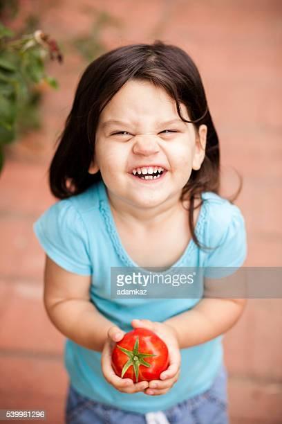 Joli petite fille avec des tomates fraîchement cueillies dans le jardin