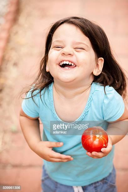 Niedlich kleines Mädchen mit frisch geerntetem Tomaten vom Garten