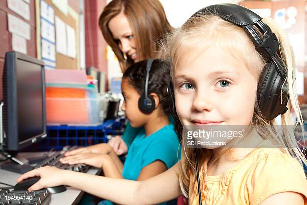 Cute Little Girl With Headphones Working on Computer at School