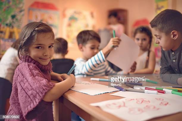 Cute little girl with her friends in a preschool.