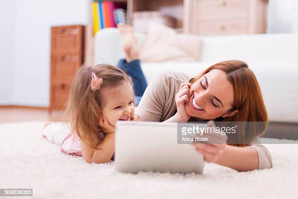 Cute little girl with mom using digital tablet at home. Debica, Poland