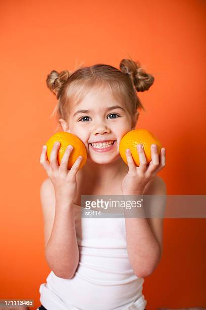 Cute Little Girl with Oranges on Orange Background