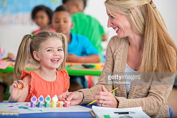 Cute little girl with pigtails laughing while painting in daycare