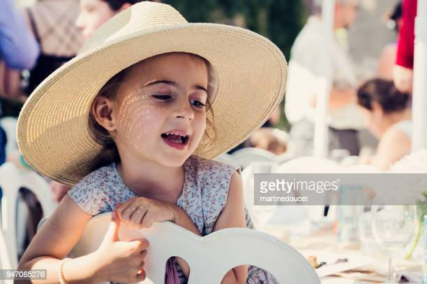 "cute little girl with too big at family reunion. - ""martine doucet"" or martinedoucet stock pictures, royalty-free photos & images"