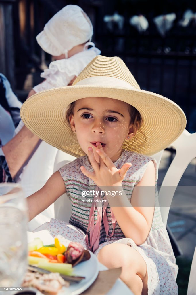 Cute little girl with too big hat eating outdoors at family reunion. : Stock Photo