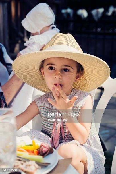 Cute little girl with too big hat eating outdoors at family reunion.