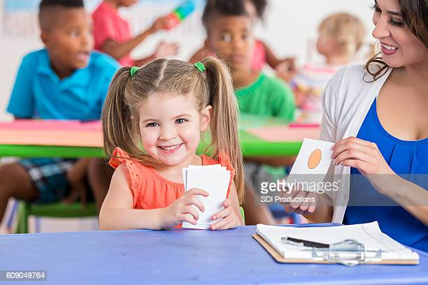 Cute little girl working on flashcards with daycare teacher