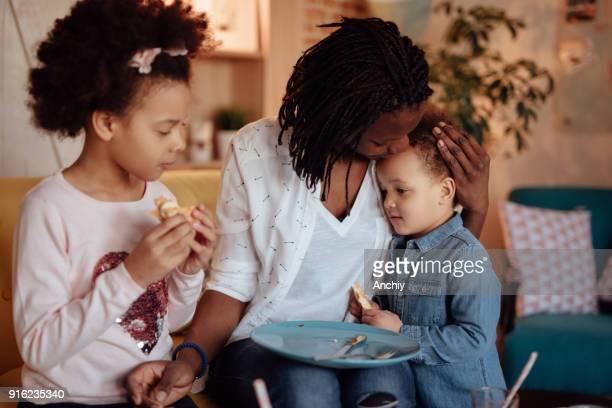 かわいい女の子のママの朝食を食べて - interracial cartoon ストックフォトと画像