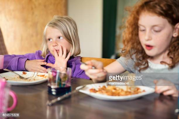 """cute little girls eating lasagna at home. - """"martine doucet"""" or martinedoucet stock pictures, royalty-free photos & images"""