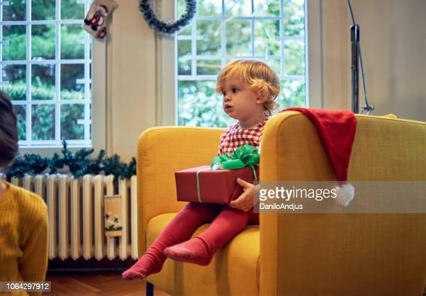 cute little girls holding her christmas present - 2 5 months stock pictures, royalty-free photos & images