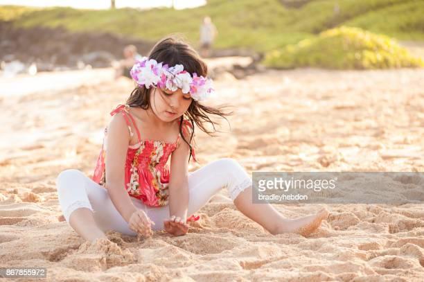 cute little hawaiian girl play with sand on beach - hawaiian lei stock pictures, royalty-free photos & images