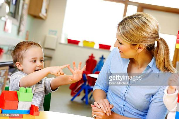 Cute little kid with teacher playing in play room