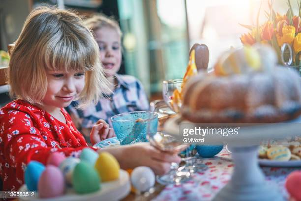 cute little kids having fun on a decorated easter table - easter cake stock pictures, royalty-free photos & images