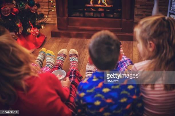 Mignons petits enfants en Pyjamas et Noël chaussettes assis en face de la cheminée