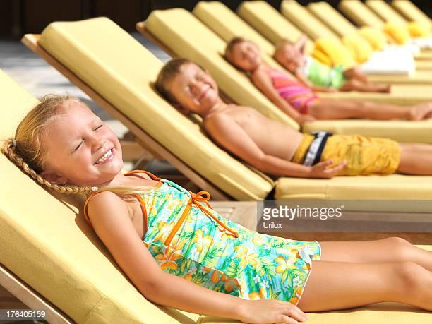 carino piccolo bambino prendere il sole in una piscina - girls sunbathing foto e immagini stock