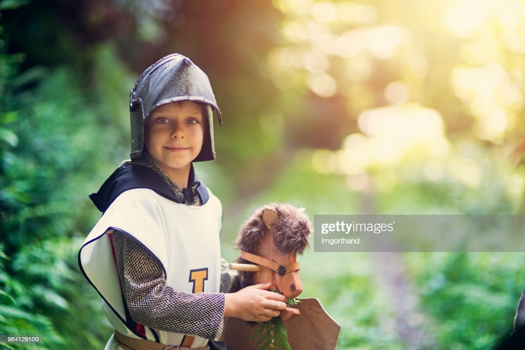 Cute little knight feeding his horse in forest : Stock Photo